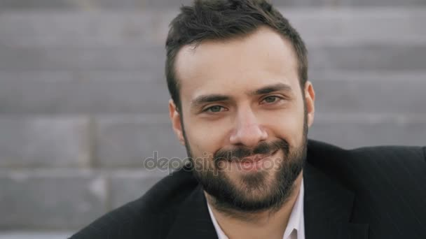 Detailní záběr portrét vousatého mladý podnikatel úsměvu a pohledu do kamery v ulici venku