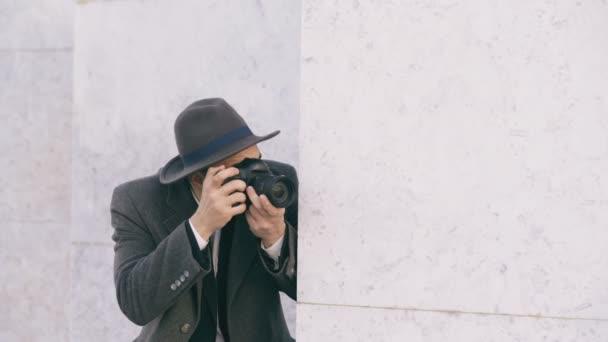 junger Paparazzi-Mann mit Hut fotografiert Prominente vor laufender Kamera, während er hinter der Mauer spioniert