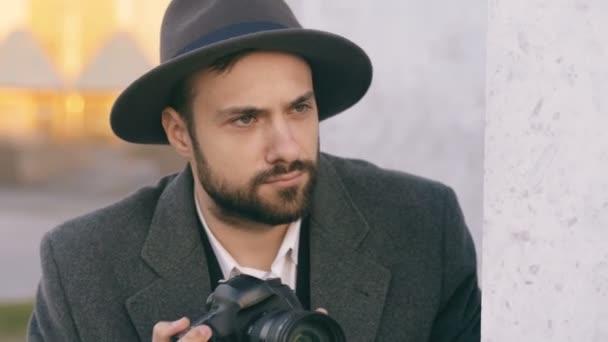 Nahaufnahme des jungen Paparazzi Mann mit Hut fotografiert Promis vor der Kamera beim Spion hinter der Wand