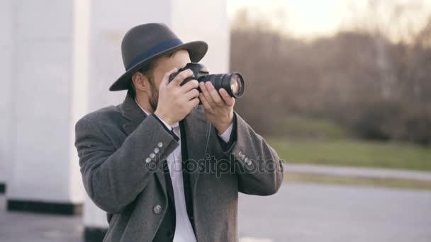Stylish young photographer man in hat standing outdoors and photographing tourist sightseeings during travel