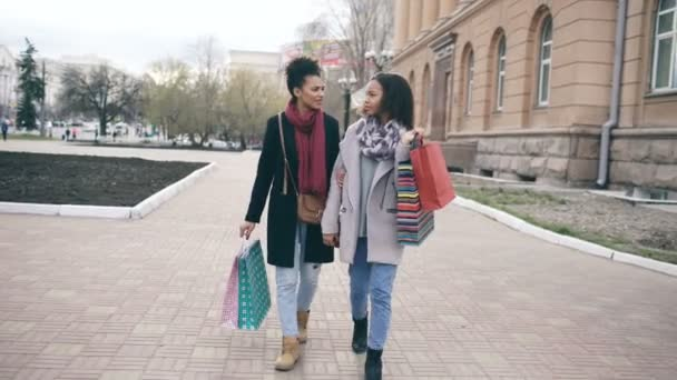 Dolly záběr dvě atraktivní smíšený závod žen s nákupní tašky se těší jejich chůze po ulici. Přítelkyně se bavit po návštěvě mall