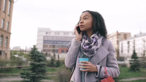 Dolly Shot von attraktiven Mischling Rennen Mädchen sprechen Smartphone und Kaffee trinken Spaziergänge in der Stadt Straße mit Taschen. junge Frau läuft nach Einkaufszentrum-Verkauf