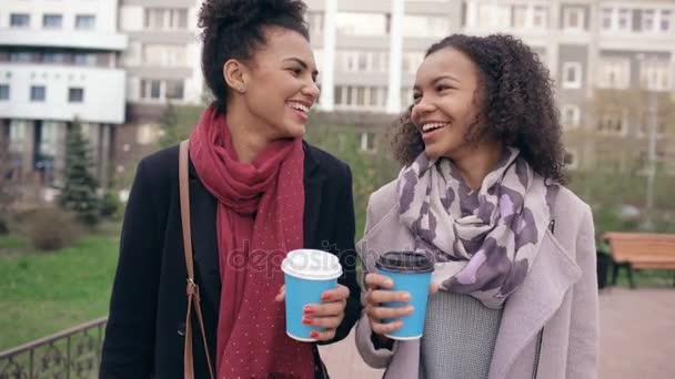 Dolly Detailní záběr dvě krásné Smíšené rasy žena přátel pít kávu a rozhovory po nakupování a procházky městem ulice