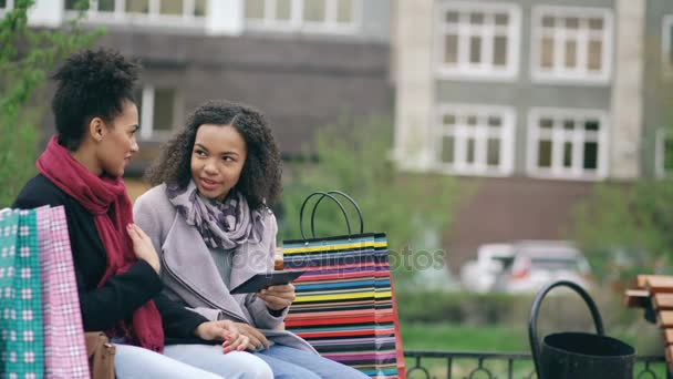 Két vonzó kevert nő a bevásárló szatyrok ül a padon, és segítségével a tábla-PC részére internet szörfözés. Boldog meg szórakozás után látogat a mall értékesítési
