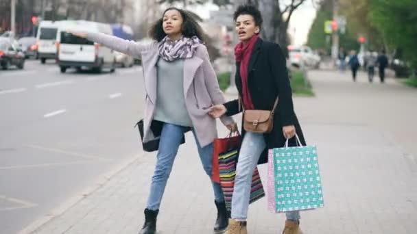Dvě atraktivní afroamerické ženy s nákupní tašky volá taxi cab při návratu z Obchoďáku prodeje