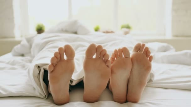 Closeup mladého páru, krásné a milující hrát a tančit své nohy pod dekou při probuzení se v posteli ráno