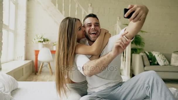 Young beautiful and loving couple take selfie picture on smartphone camera and kiss while sitting in bed at the morning