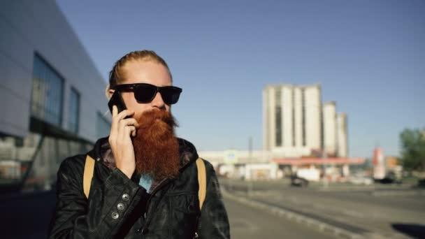 Dolly záběr mladý vousatý bokovky člověka v sluneční brýle s úsměvem a Nový Ostružina Bouře smartphone cestách městské ulice