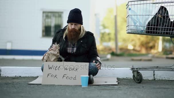 Mladý muž pomáhá bezdomovec a dávat mu nějaké peníze a zároveň žebrák pít alkohol a sedět poblíž nákupního košíku na ulici