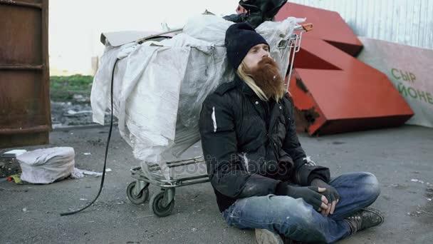 junger bärtiger Obdachloser sitzt an kalten Wintertagen auf einem Bürgersteig in der Nähe von Einkaufswagen und Müllcontainern