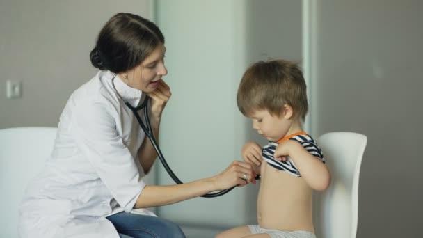 Mladá žena doktor poslouchá malého chlapce s stetoskop v ordinaci
