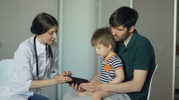 Mladá žena doktor mluvil s otcem malého chlapce pomocí tabletového počítače v ordinaci