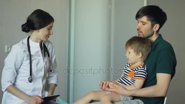 Junge Ärztin im Gespräch mit Vater des kleinen Jungen in Arztpraxis