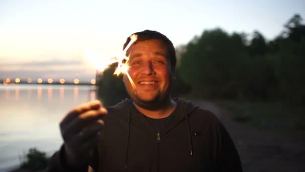 Portrét mladých usmívající se muž s prskavka slaví na beach party