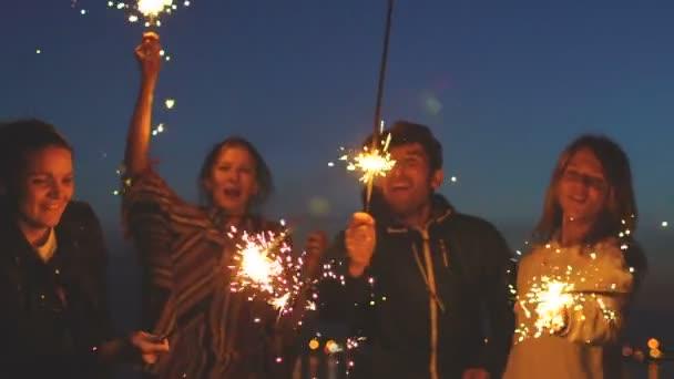 Slowmotion csoport fiatal barátai, amelyek egy beach party. Meg táncolni, és ünnepli csillagszórók twilight naplemente