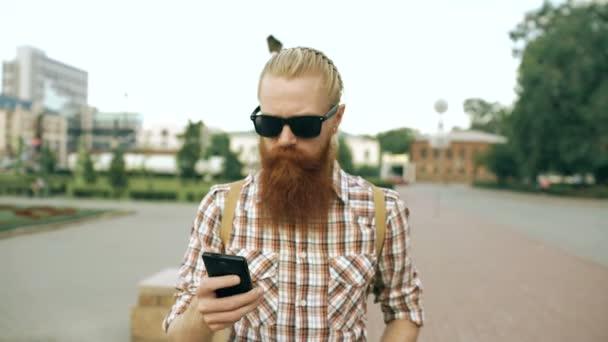 Steadicam záběr vousatý turistické člověka s batohem walking street a pomocí smartphone pro Zobrazit mapu venku