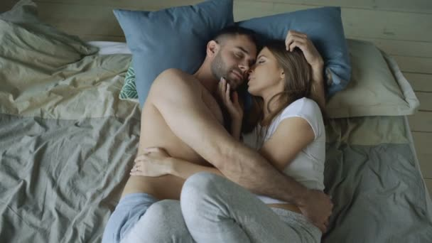 junges schönes und liebevolles Paar küsst sich morgens auf dem Bett