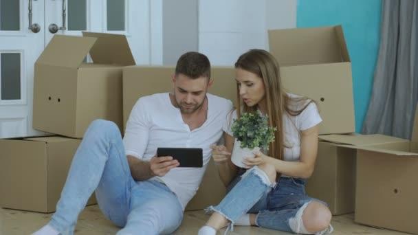 Mladý pár sedící na podlaze pomocí tabletového počítače po reloction v jejich novém domově
