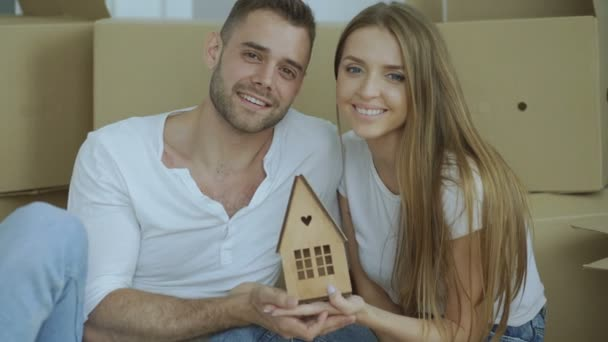Portrait of happy couple in new home. Young smiling family holding small wodden house and looking into camera