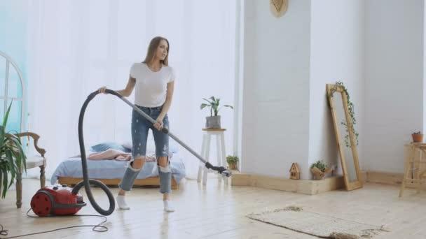 junge Frau hat Spaß beim Hausaufräumen mit Staubsauger tanzen und singen zu Hause