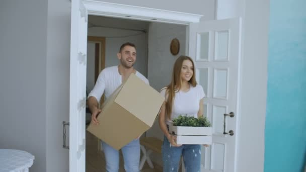 Young happy couple walking in new house after relocation and kiss each other