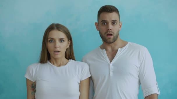 Portrét mladého páru aktivně překvapující a přemýšlel, pohledu do kamery na modrém pozadí