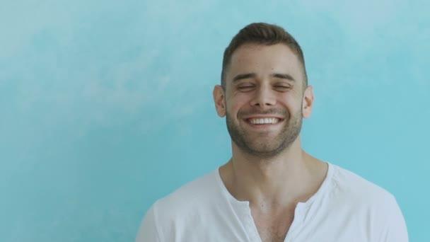 Slowmotion z mladých usmívá a směje se člověk dívá do kamery na modrém pozadí