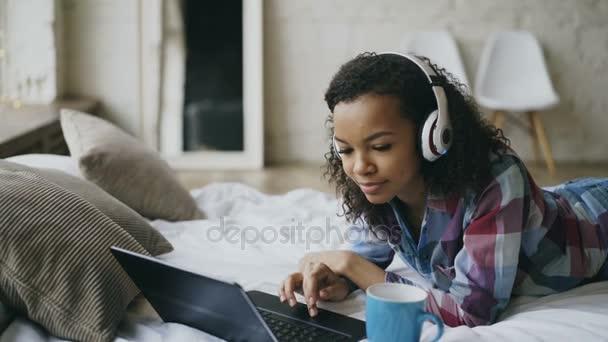 Mladá kudrnaté africká americká žena těší poslouchat hudbu na notebooku, když ležel na posteli