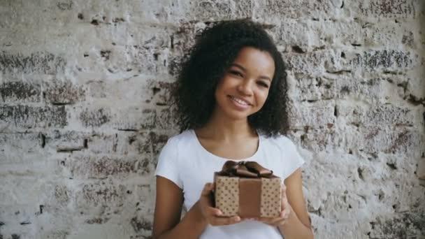 Portrét mladé afroamerické ženy drží dárkovou krabičku a úsměv do kamery