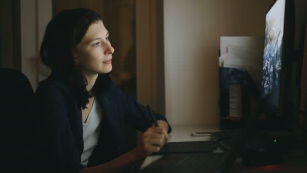 Koncentrált nő tervező dolgozik office grafikus tábla és a laptop számítógép használata éjjel