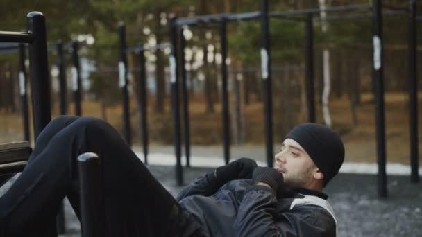 Uomo giovane atleta che fa esercitazione sui muscoli addominali alla palestra allaperto nel parco di inverno