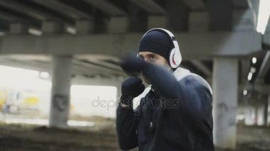 Dolly shot of sportive man boxer in headphones training punches in urban location outdoors in winter