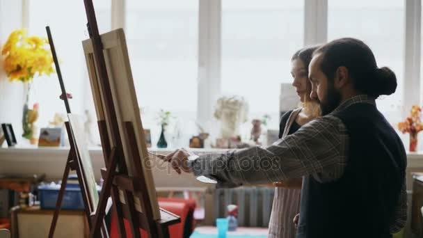 Skilled artist man teaching young girl to drawing paintings and explaining the basics in art studio