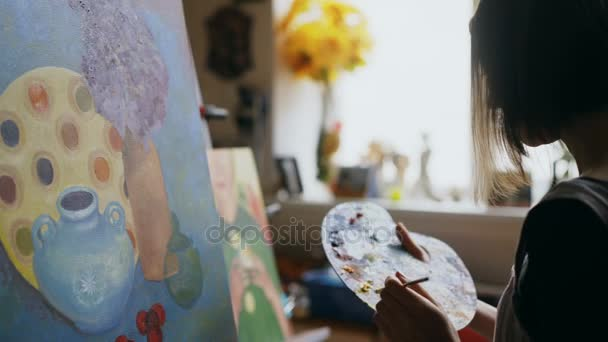 Close-up of young artist woman mix paints with brush in palette and painting still life picture on canvas in art studio