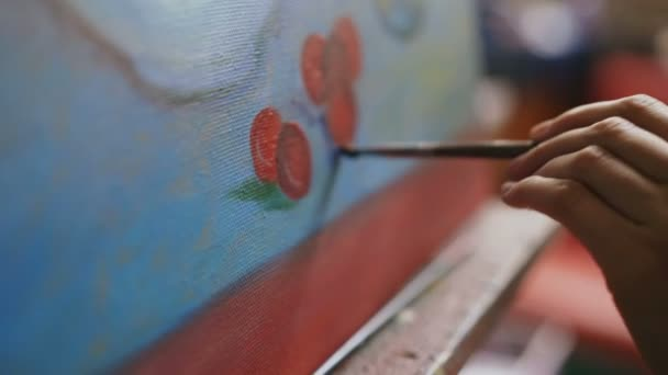 7954cb502 Close-up of artist womans hand with brush painting still life picture on  canvas in art studio