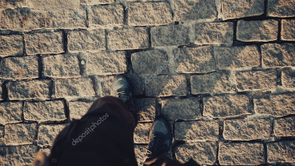 Top view POV of man in shoes walking at historical ancient sidewalk