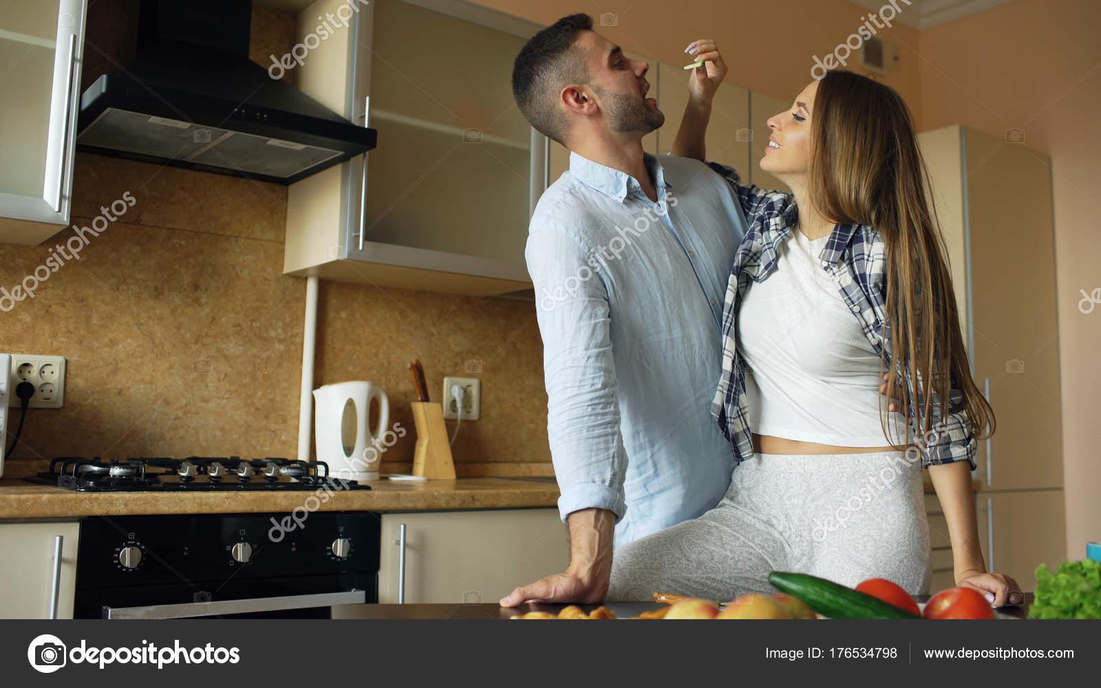 Glückliches junges Paar in der Küche. Attraktive Frau, die ihrem ...