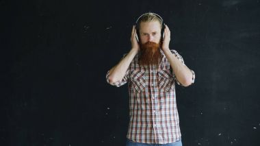 portrait of bearded young man with headphones looking into camera