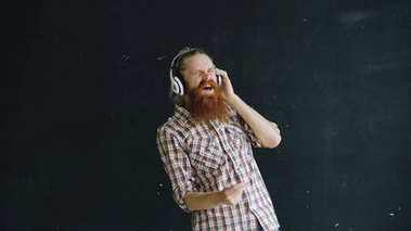 Portrait of bearded young man puts on headphones and dancing while listen to music on black background