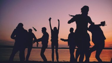Silhouette of Group young dancing people have a party at beach on sunset