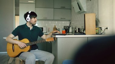 Cheerful young man with headphones sitting at kitchen learning to play guitar using laptop computer at home