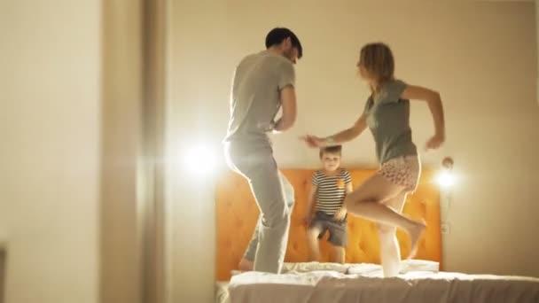 Šťastná rodina s malým synem, tančit a bavit se na posteli doma večer před spaním