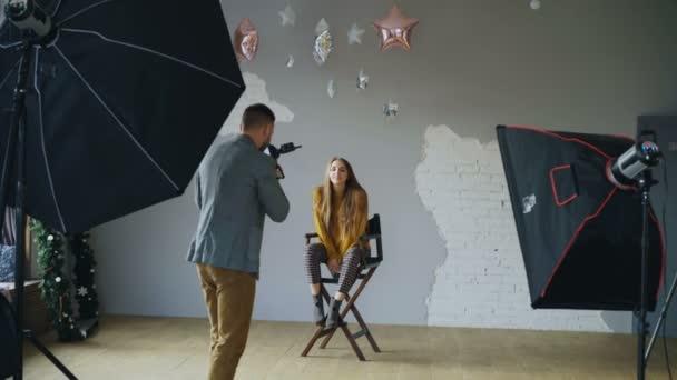 junge schöne Frau Modell posiert für Fotograf, während er mit einer Digitalkamera in Fotostudio drinnen schießt