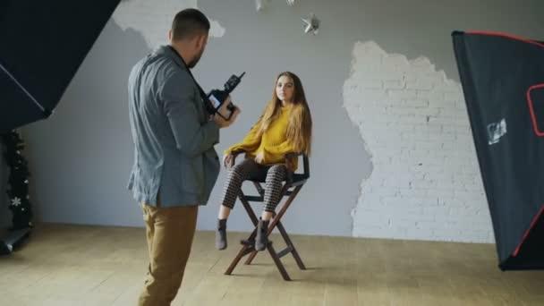 professioneller Fotograf fotografiert Modell auf Digitalkamera im Fotostudio