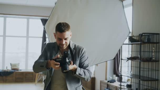 Mladý muž fotograf pracující ve fotoateliéru fotografování modelu na digitální fotoaparát