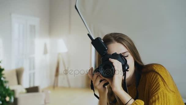 Mladá žena fotograf pracující ve fotoateliéru fotografování mužského Modela na digitální fotoaparát