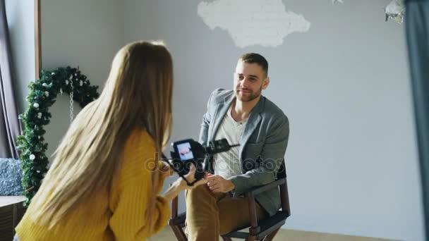 Mladý atraktivní model muž pózuje pro fotograf ženu, zatímco ona je fotografování s digitálním fotoaparátem ve fotoateliéru uvnitř