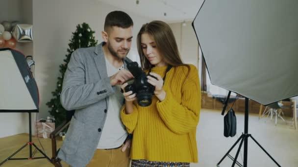 Profesionální fotograf muž krásný model dívka ve fotoateliéru uvnitř náhodné přehrávání fotek na digitální fotoaparát