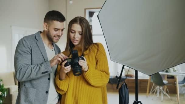 Profesionální fotograf žena ukazuje fotografie na digitální fotoaparát na atraktivní model člověka v ateliéru doma