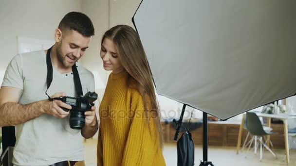 professionelle Fotograf Mann zeigt Fotos auf Digitalkamera zu Studentenmädchen bei persönlichen materclass in Fotostudio drinnen